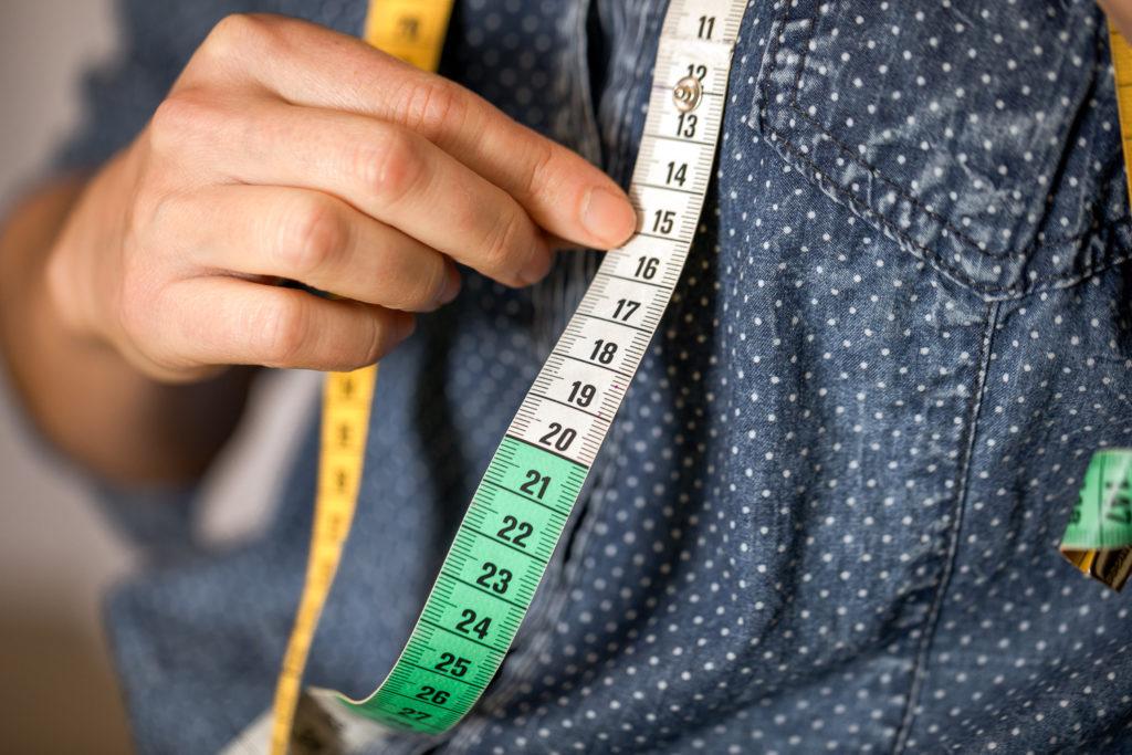 Main de couturière et mètre de couture